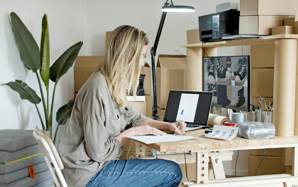zena sa laptopom sjedi za stolom